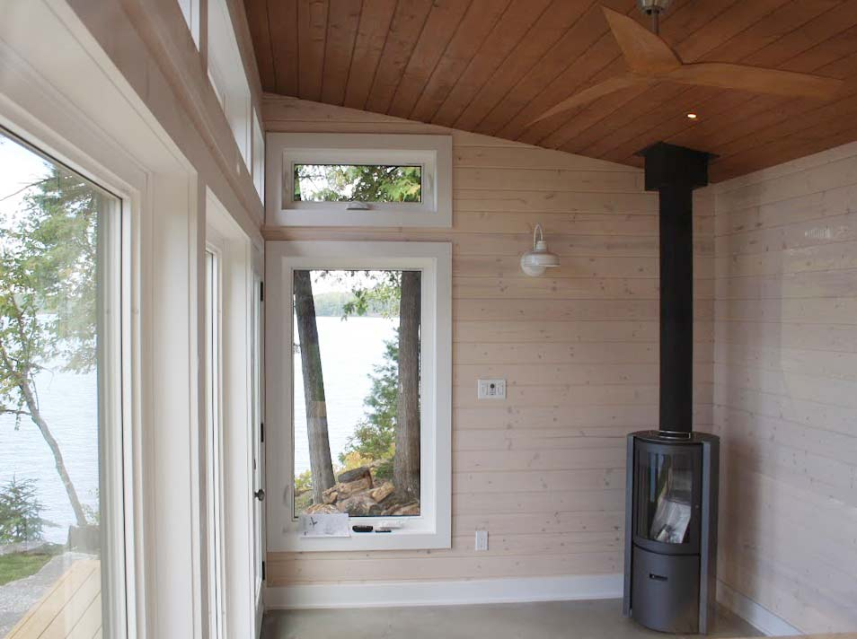 Interior view of bunkie with wood burning stove looking out onto lake